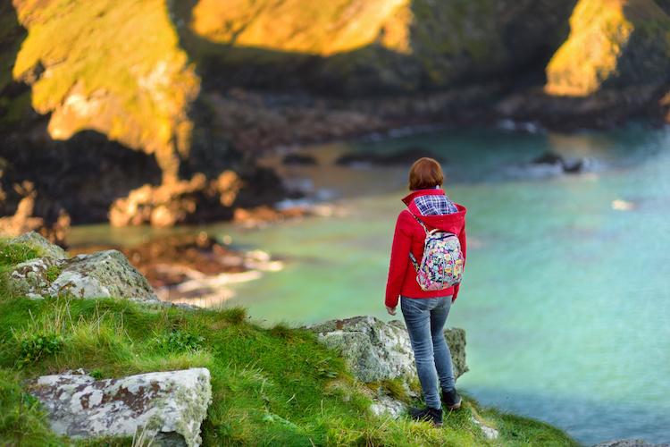 Tourist enjoying view of scenic rugged Cornish coastline